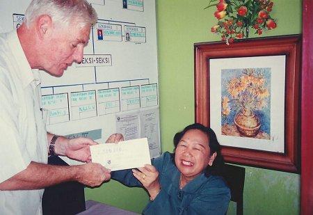 Mw. Rosalina (hoofd der school) ontvangt een bijdrage van Suvono/LKS voor de renovatie van de speelruimte, schoolplein, etc. uit handen van Pim Vroegop.